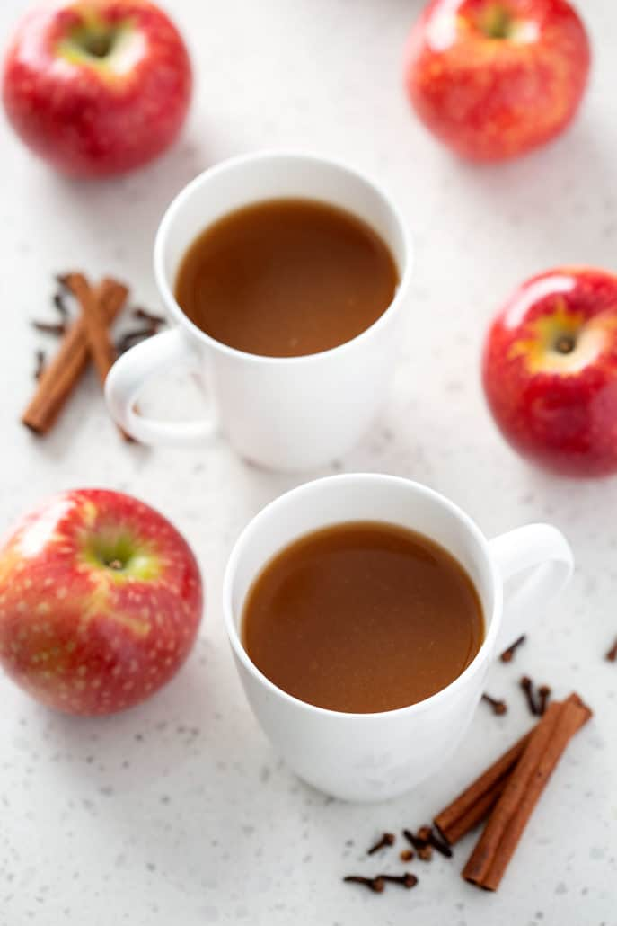 two mugs of apple cider surrounded by apples and spices