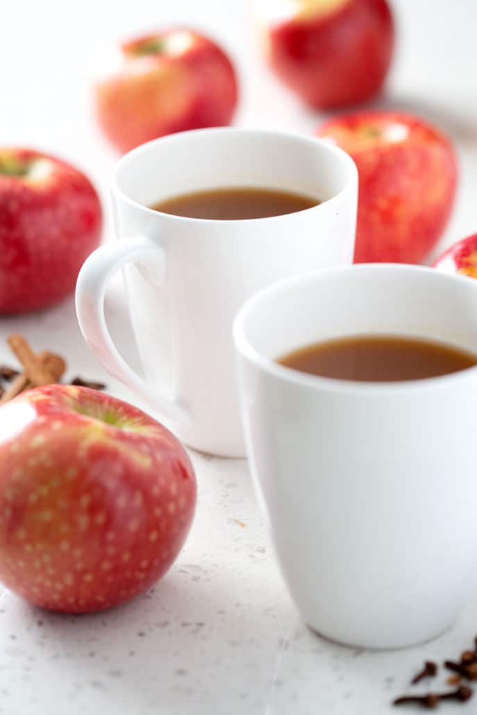 two mugs of apple cider surrounded by apples