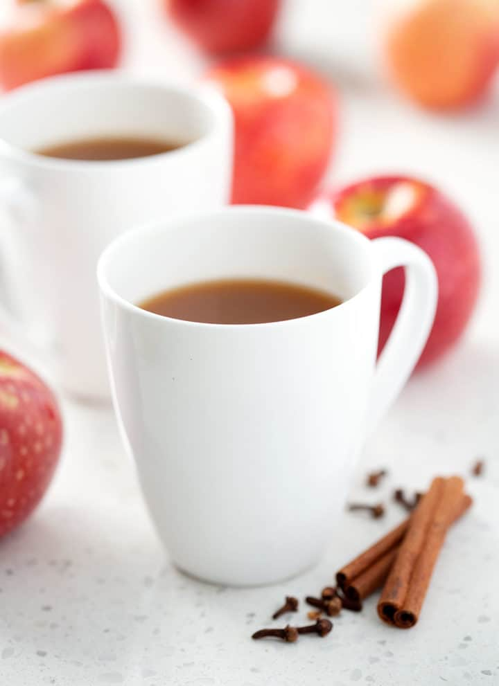 mug of apple cider surrounded by apples and spices