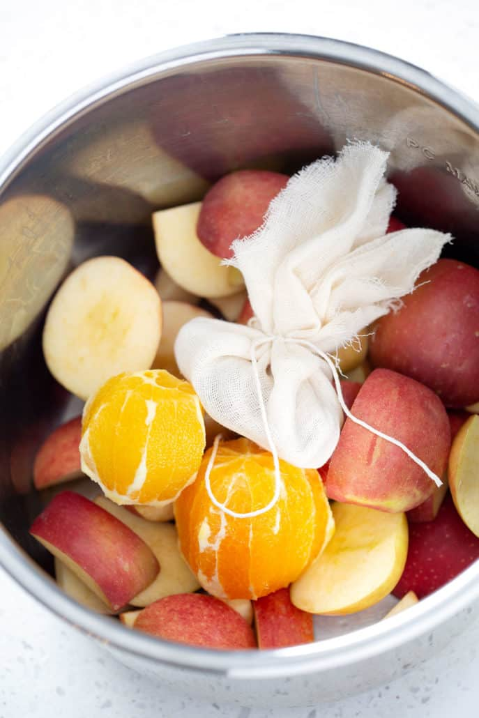 cut apples, oranges and spice sachet in instant pot