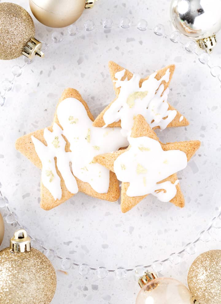 plate of cut out sugar cookies surrounded by gold ornaments