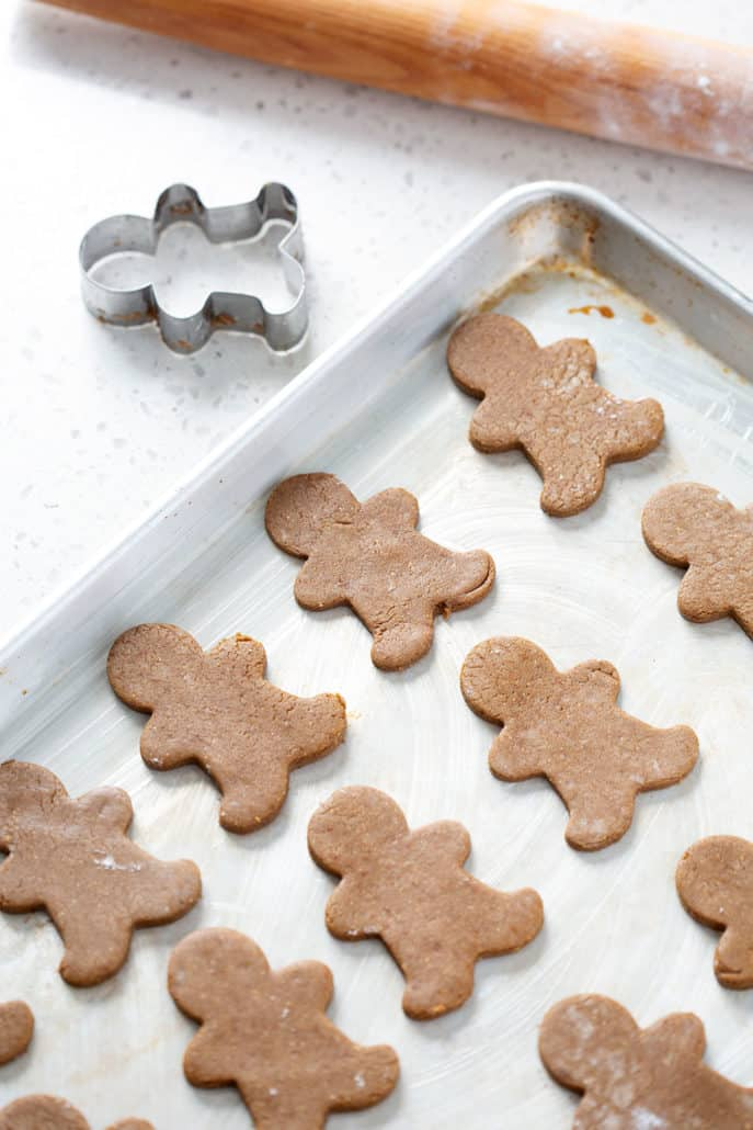 baking sheet of aip gingerbread cookies with rolling pin and cookie cutter
