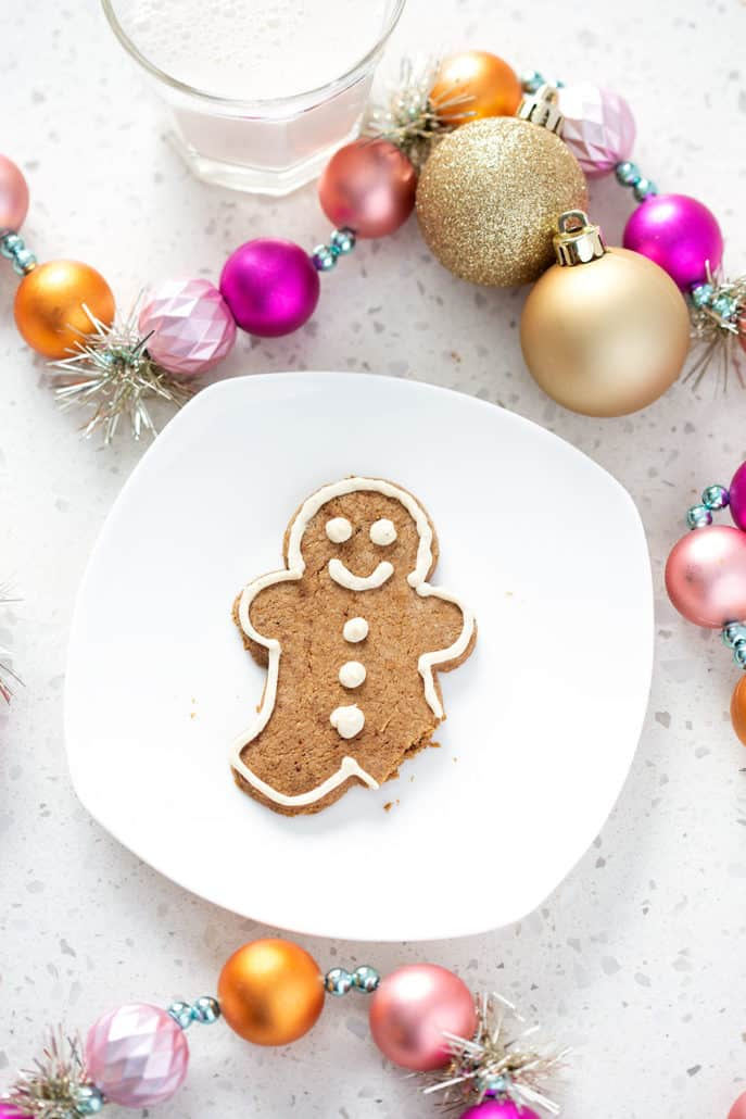 aip gingerbread cookie on white plate surrounded by Christmas ornaments