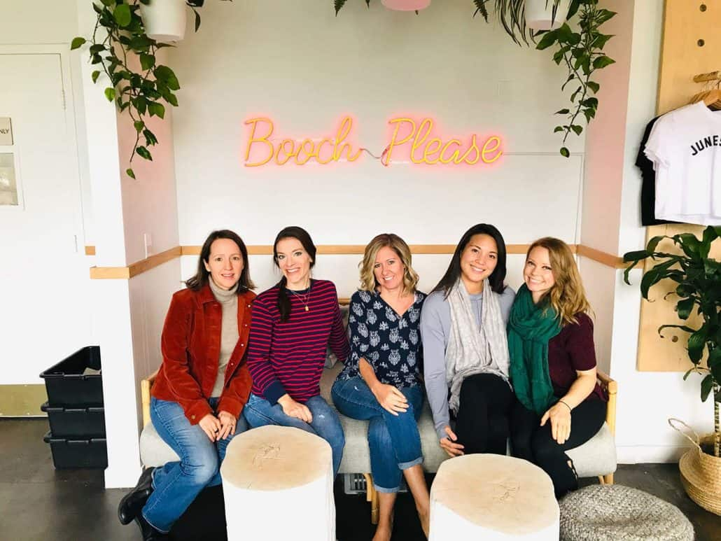 group of women sitting on couch under neon sign that says booch please