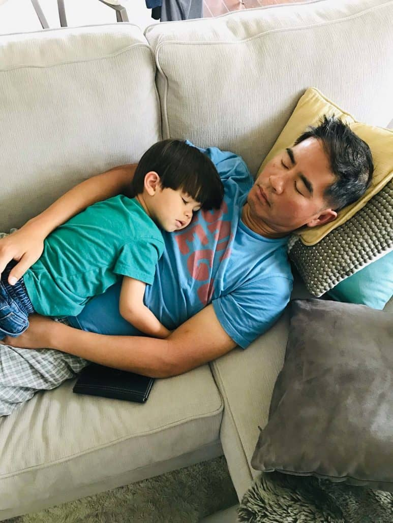 father and son sleeping on couch