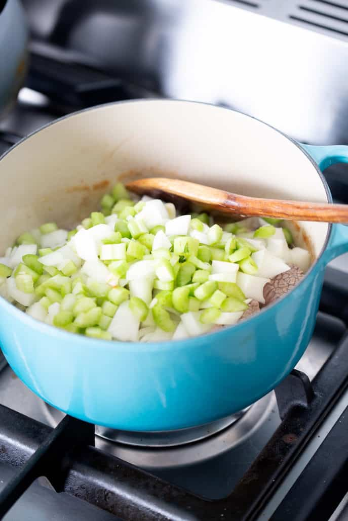 stockpot on stovetop filled with celery and onions