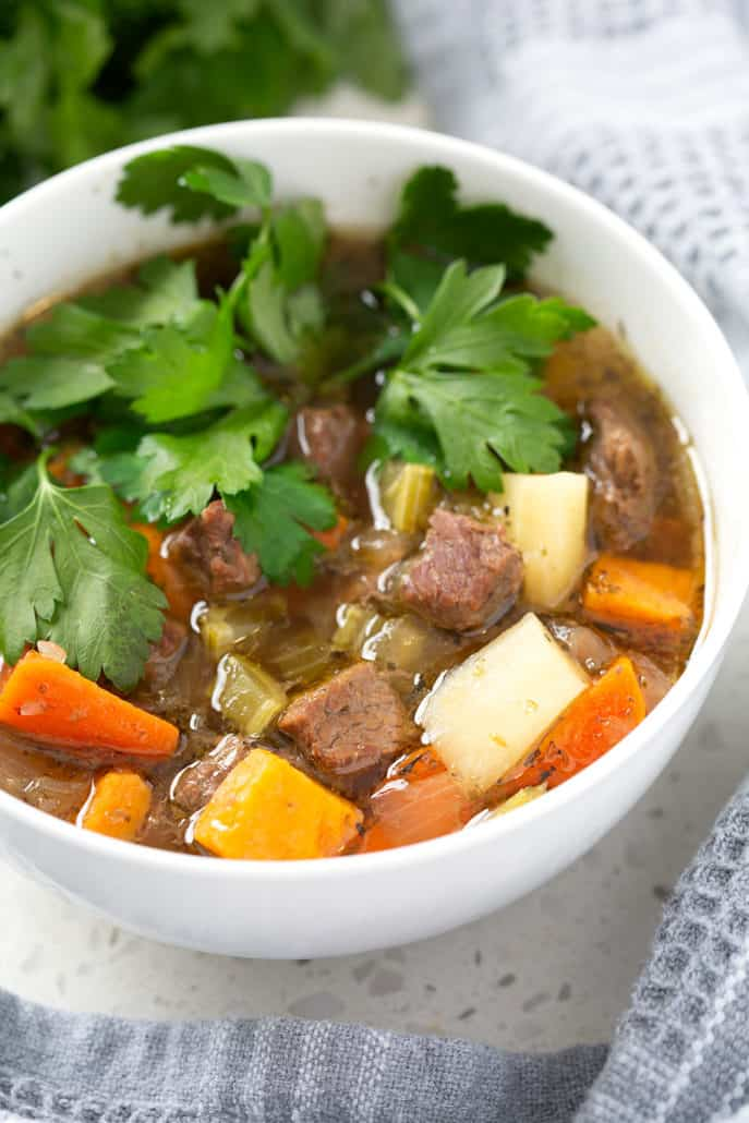 close up of bowl aip beef stew with parsley garnish