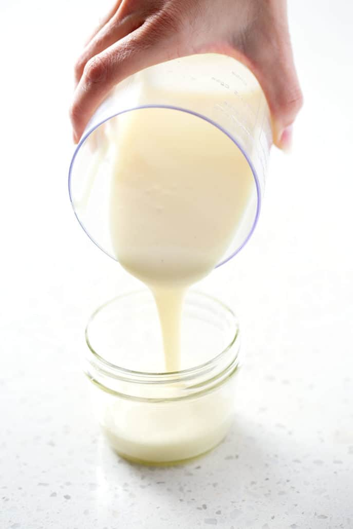pouring aip mayo (egg free mayoo recipe) into mason jar