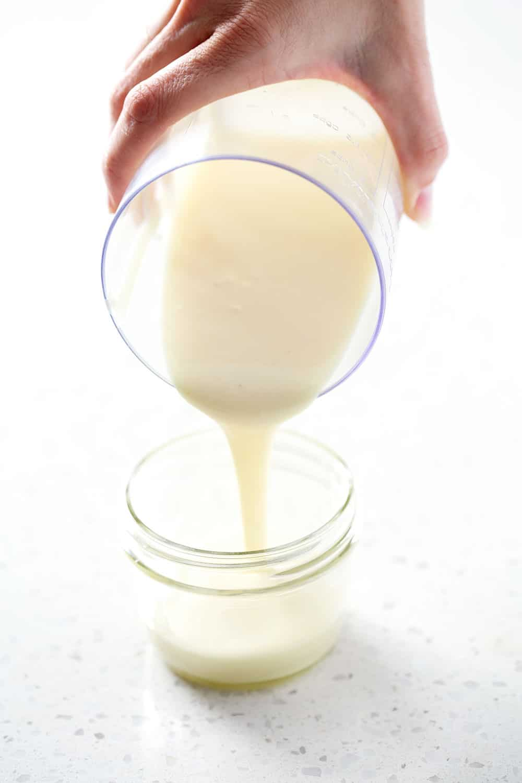 pouring aip mayo (egg free mayoo recipe) into mason jar