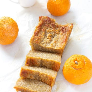 loaf of AIP Baked Cassava Cake with oranges and cup of tea