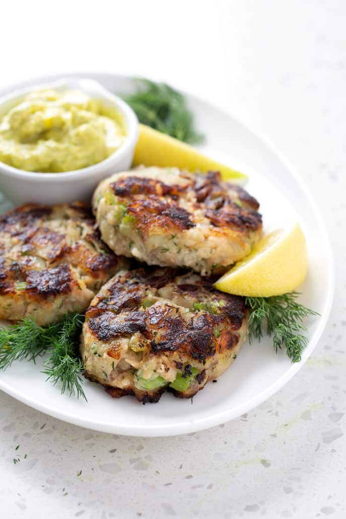 platter of aip salmon cakes surrounded by lemon slices, dill and dip