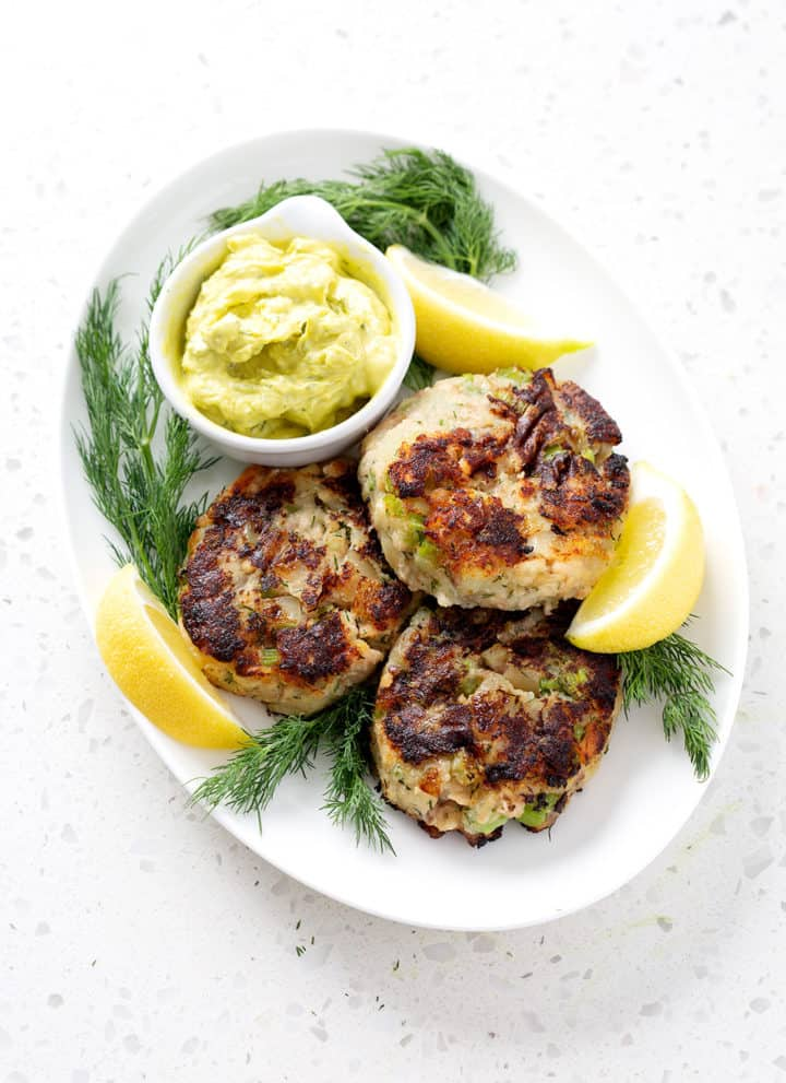 platter of aip salmon cakes surrounded by lemon slices, fresh dill and dip