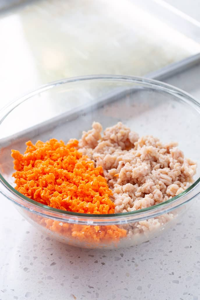Ground chicken and riced sweet potatoes in glass bowl