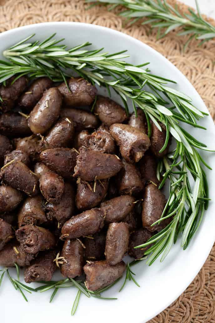 plate of rosemary chicken hearts garnished with fresh rosemary