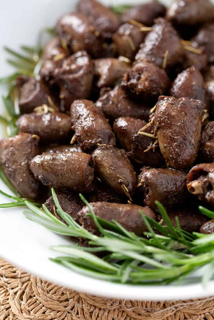 close up of chicken hearts garnished by fresh rosemary