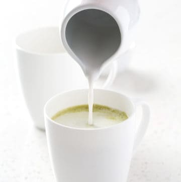 pouring coconut milk into mug of matcha green tea