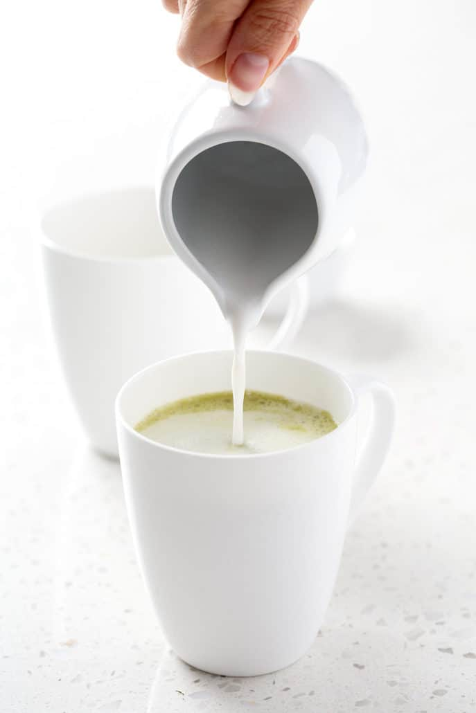 pouring coconut milk into matcha tea on white background