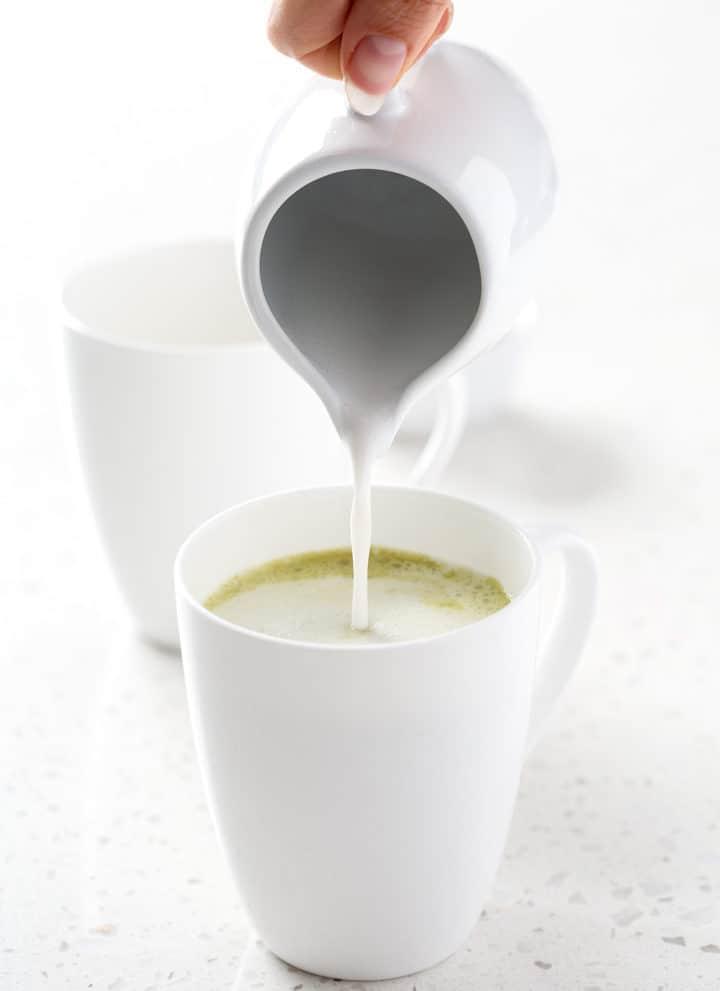pouring coconut milk into mug of matcha green tea