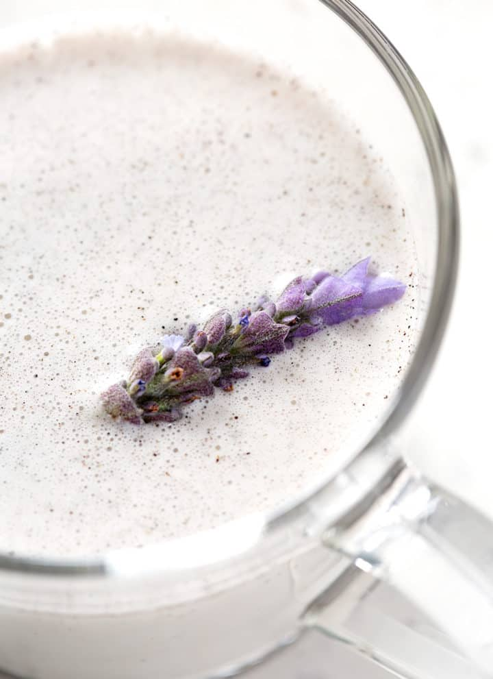 close up of cup of lavender milk tea with fresh lavender floating
