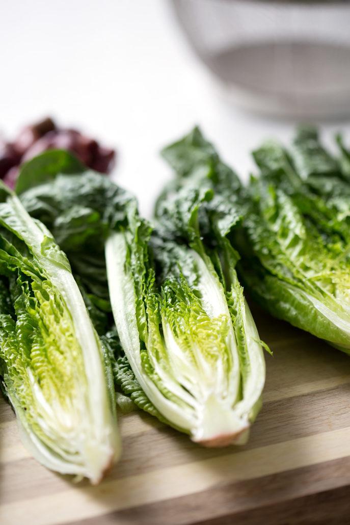 romaine lettuce cut in half on cutting board