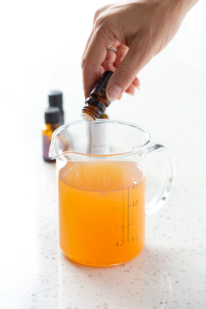 pouring essential oils in measuring cup on white background