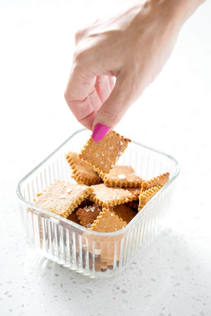 picking AIP Cassava 'Cheese' Crackers out of glass container on white background