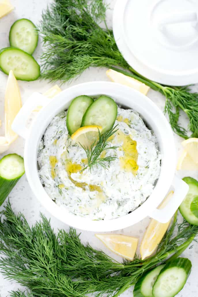 bowl of Dairy Free Tzatziki surrounded by cucumbers, dill and lemon