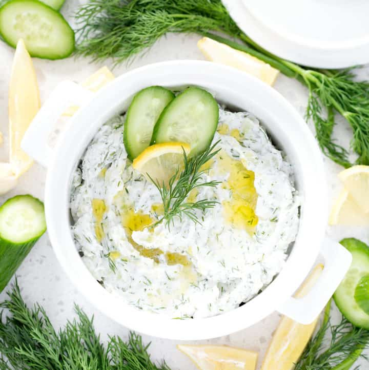bowl of dairy free tzatziki surrounded by cucumbers, lemon and dill