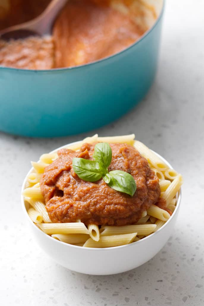 bowl of pasta with sauce and basil on top
