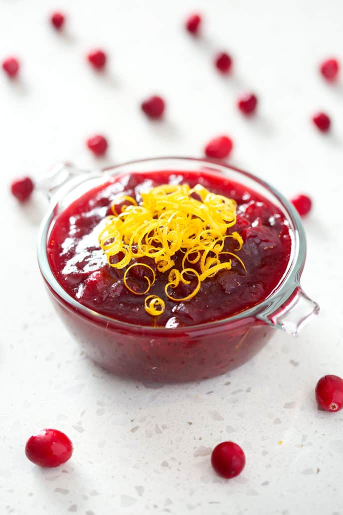 bowl of cranberry sauce garnished with orange zest surrounded by
