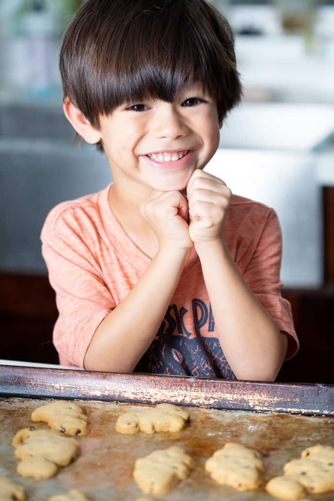 young boy smiling over baking sheet of AIP 'Chocolate' Chip Cut Out Cookies