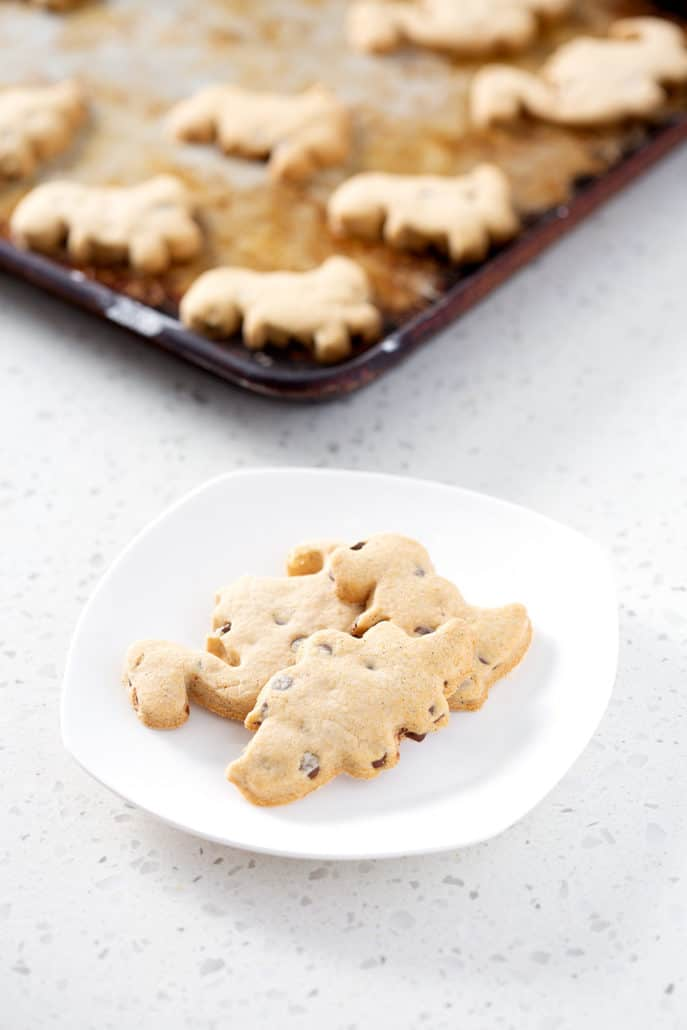 dinosaur cut out cookies on white plate with more cookies on baking sheet