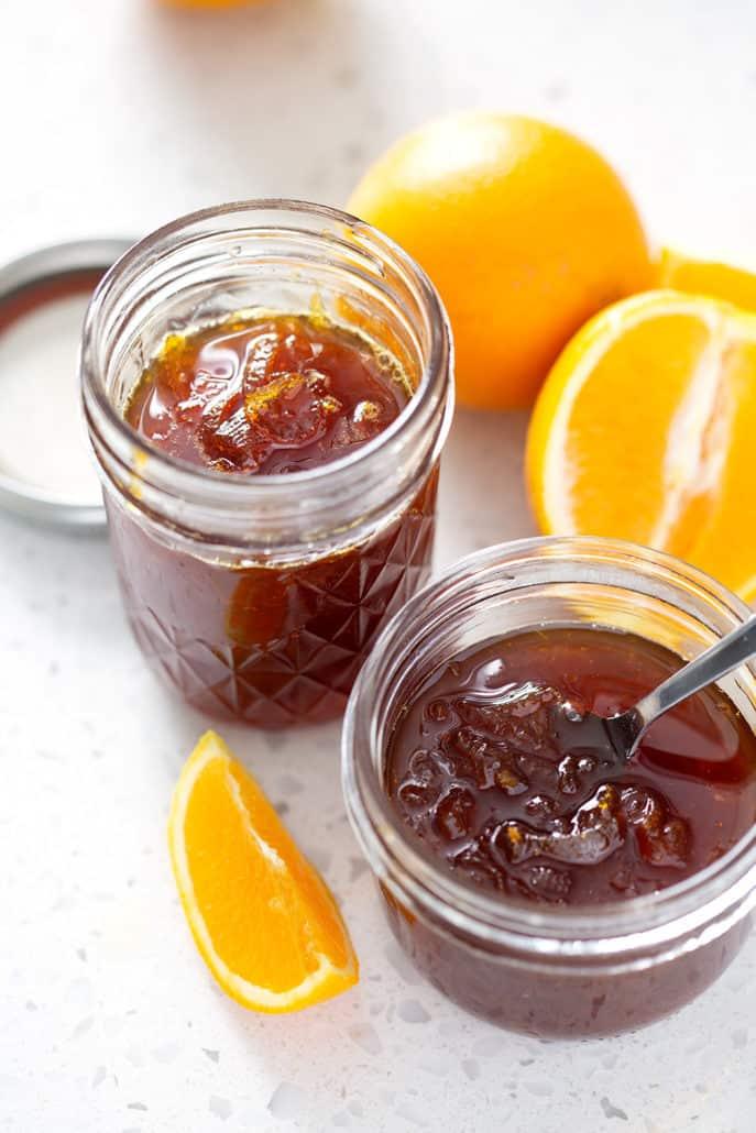 mason jars of Instant Pot Orange Marmalade with oranges