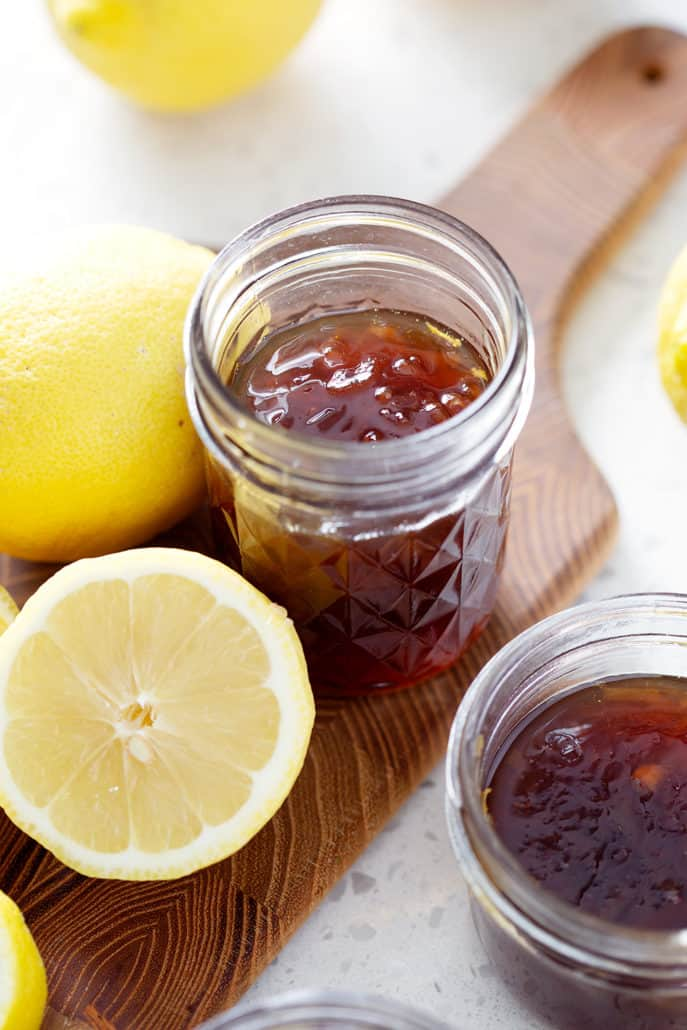 mason jars of Lemon Honey Marmalade on cutting board with lemons
