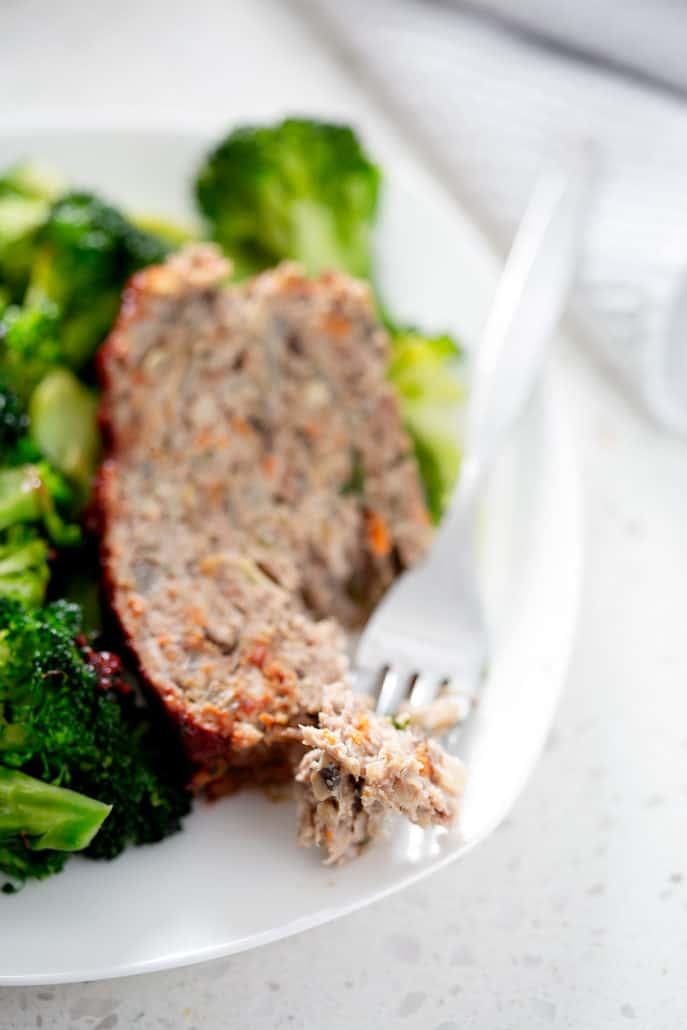 close up of meatloaf and fork with broccoli