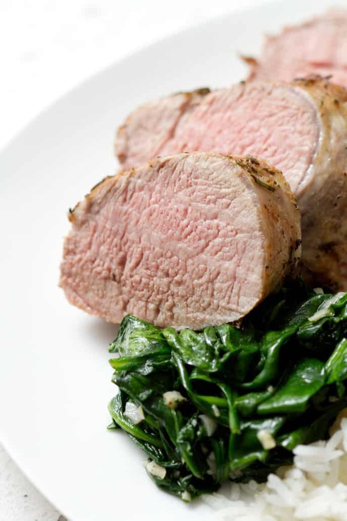 slices of AIP Pork Tenderloin with sautéed spinach on plate