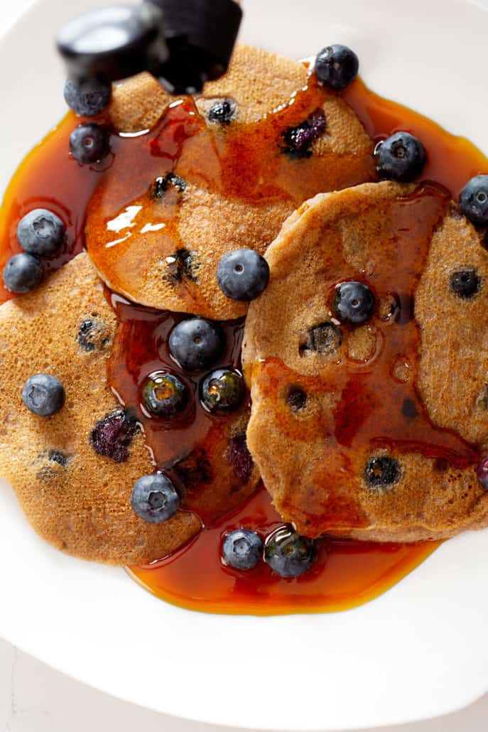 pouring maple syrup on AIP Blueberry Pancakes from above