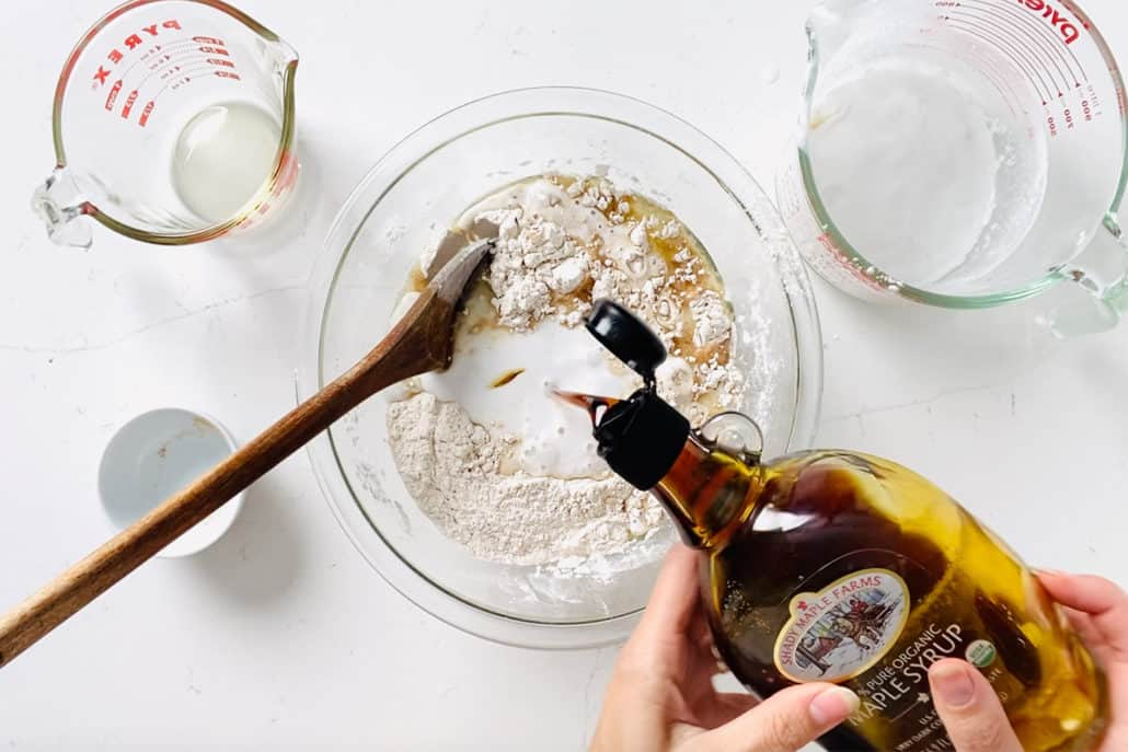 pouring maple syrup into mixing bowl surrounded by measuring cups and wooden spoon