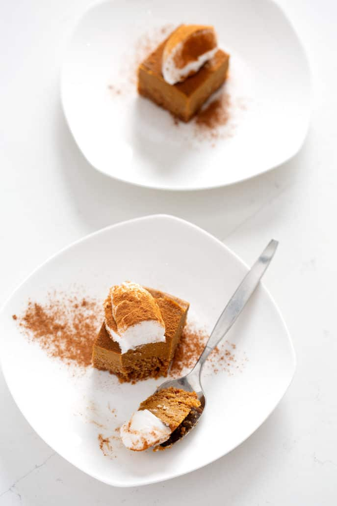 AIP Pumpkin Pie Bars on white plates with topping on what counter